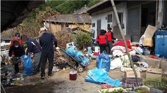 사회봉사명령대상자들이 집주위를 깨끗이 청소하고 있다.(사진제공=창원준법지원센터)