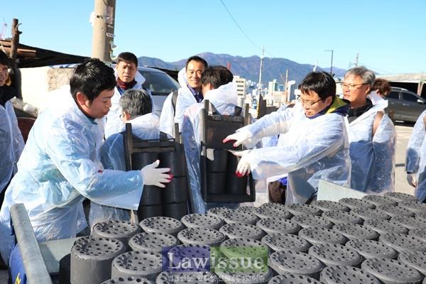 부산선관위 선한모임 회원들이 연탄을 지게에 올리고 있다.